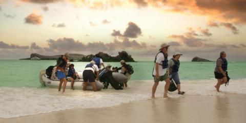 People dragging a boat out of the seas around the galapagos islands