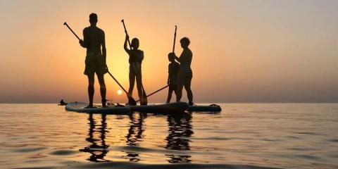 Family paddleboarding at the Aeolian Village Beachclub at sunset.