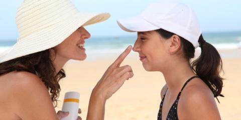 Mother applying sun cream to her daughter